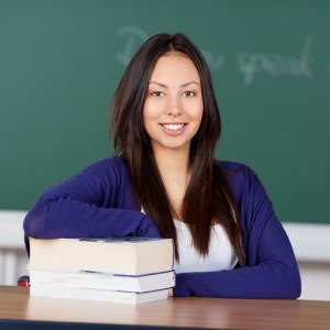 http://www.dreamstime.com/stock-photo-young-asian-woman-sitting-school-desk-leaning-stack-books-image31326820
